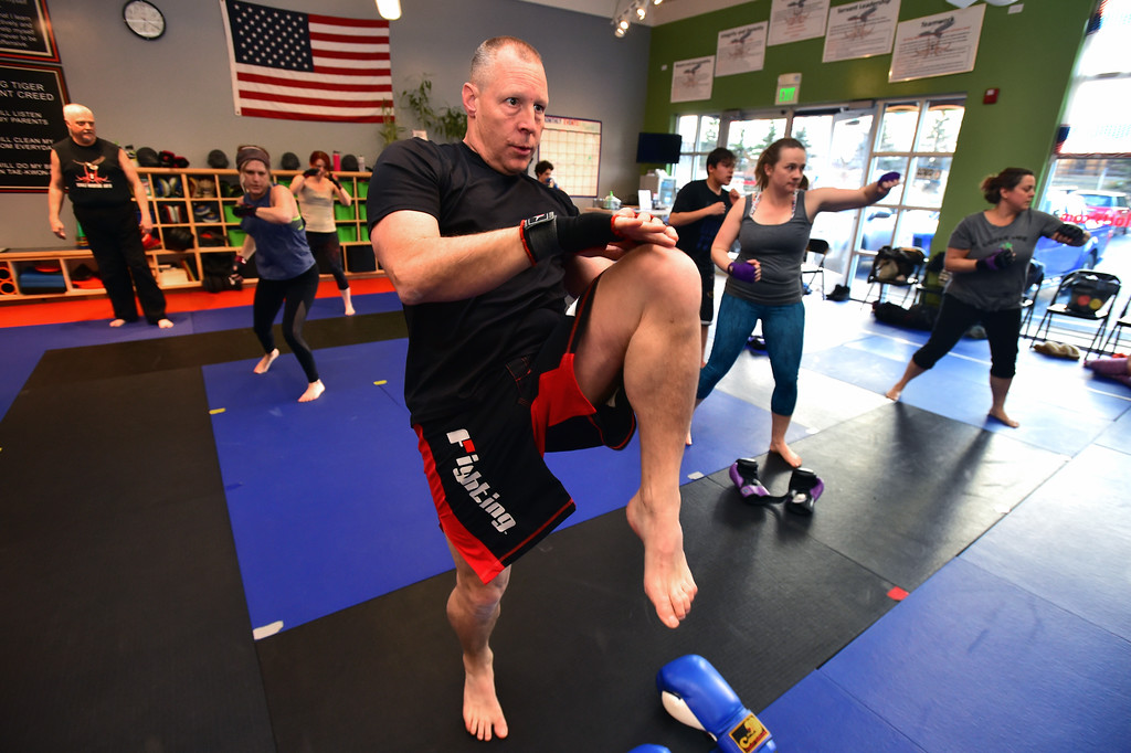 . John Kemp throws knee strike combinations in the warm up in the phase of the Adult Cardio Kickboxing class at Schilz Martial Arts in Lafayette on Monday. For more photos go to dailycamera.com Paul Aiken Staff Photographer March 12, 2018.