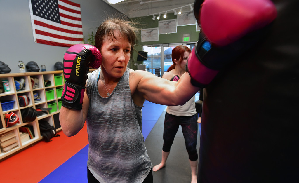 . Barb Woodbury hits a bag with a backfist in the Adult Cardio Kickboxing class at Schilz Martial Arts in Lafayette on Monday. For more photos go to dailycamera.com Paul Aiken Staff Photographer March 12, 2018.