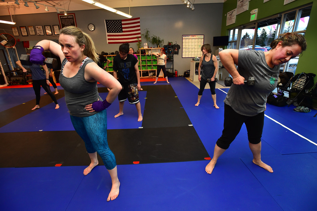 . Shani O\'Brien, left, and and Angie Barbetta in the weight lifting segment of the Adult Cardio Kickboxing class at Schilz Martial Arts in Lafayette on Monday. For more photos go to dailycamera.com Paul Aiken Staff Photographer March 12, 2018.