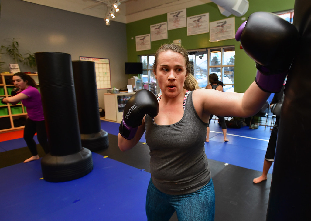 . Shani O\'Brien backfists a bag in the Adult Cardio Kickboxing class at Schilz Martial Arts in Lafayette on Monday. For more photos go to dailycamera.com Paul Aiken Staff Photographer March 12, 2018.