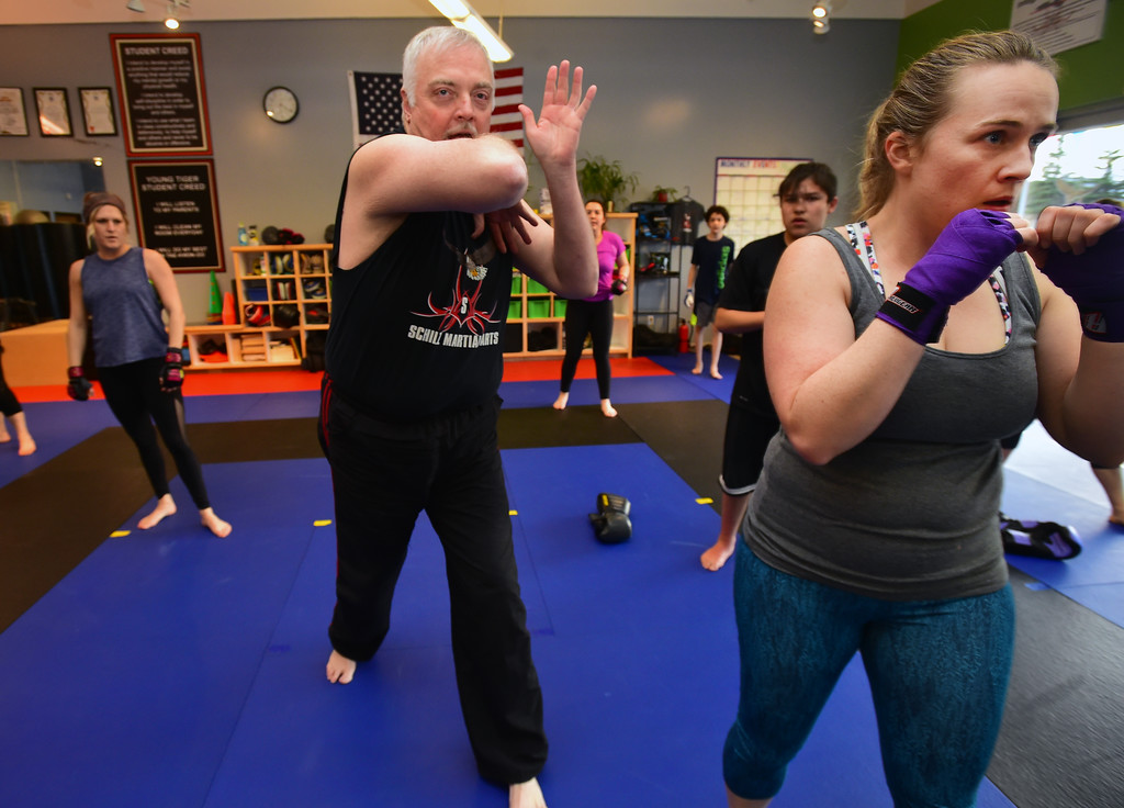 . Kru Kevin Schilz calls out a series of techniques as Shani O\'Brien listens in the Adult Cardio Kickboxing class at Schilz Martial Arts in Lafayette on Monday. For more photos go to dailycamera.com Paul Aiken Staff Photographer March 12, 2018.