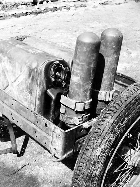 "TWO RELOADS OF FUEL, contained in two five gallon GI water cans with open mouths, and 2 nitrogen cylinders, lashed to the can handles with web belts and M-I rifle slings, are shown after they have been secured to the cart. Note how the cans, placed on their sides, plus the nitrogen cylinders (upside down) just reach the cart's width. August 1944 - Pavuvu, Russell Island<br /> <br />  <a href=""http://www.historylink101.com/wwII_b-w/marines/prplaneguns/index.html"">http://www.historylink101.com/wwII_b-w/marines/prplaneguns/index.html</a>"