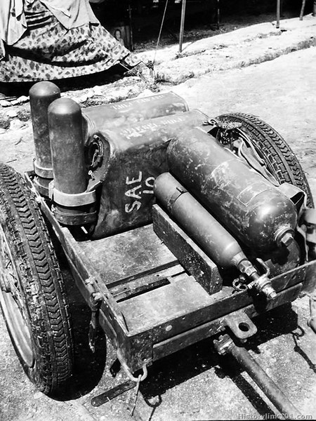 "ONE FLAME-THROWER fuel unit is then placed in the cart with the cylinder botrtoms against the sides of the water cans. The latter, of course, have been filled with fuel, diesel oil in this case. Note how the nitrogen cylinder rests against the chock, which holds the unit secure. The valve clears the edge of the cart. August 1944 - Pavuvu, Russell Island<br /> <br />  <a href=""http://www.historylink101.com/wwII_b-w/marines/prplaneguns/index.html"">http://www.historylink101.com/wwII_b-w/marines/prplaneguns/index.html</a>"