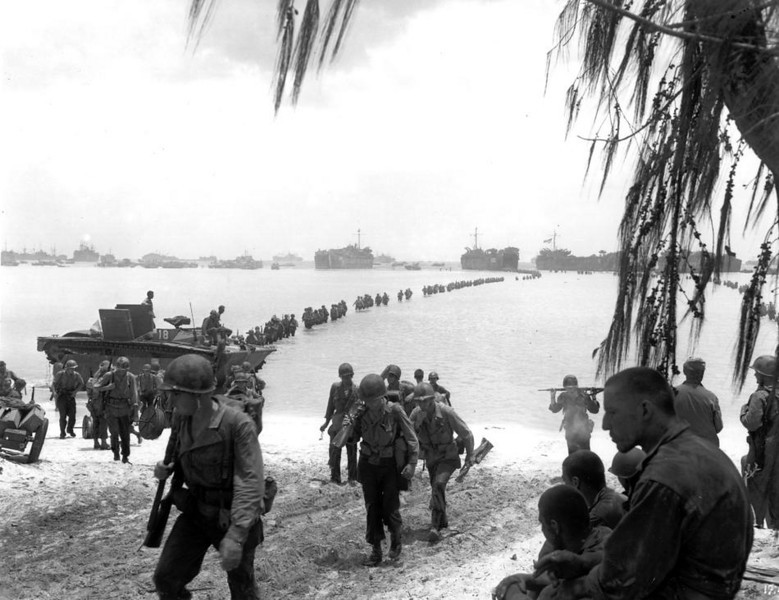 July 1944: U.S. Army reinforcement troops are seen as they disembark from LST's in the background and proceed across the coral reef toward Saipan beach, Mariana Islands. (AP Photo)