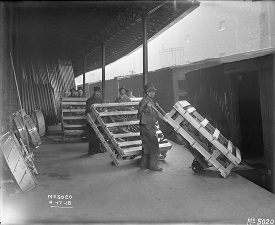 "Title:  Workers Load Wagon Components onto Railcar <br /> <br /> Description:  Workers loading wooden crates containing wagon components onto rail cars at International Harvester's McCormick Works. The crates are labeled ""from Army inspector of ordinance; International Harvester Co.; McCormick Works."" The pieces were likely manufactured under a military contract with the U.S. government.<br /> <br /> Wisconsin Historical Images Image ID:  8984 <br /> <br /> Creation Date:  April"