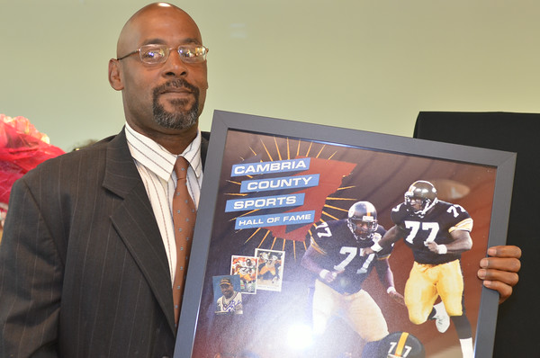 Cambria County Sports Hall of Fame inductee Carlton Haselrig poses with his commemorative poster. Haselrig was honored again in 2014 for his time with the Pittsburgh Steelers.