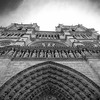 Black and white image of the facade of Notre Dame de Paris, detail of west entrance to the cathedral.