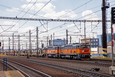 'Goggles' 753-710-3 and 753-707-9 exit Praha Liben freight yard on a train of empty car transporter wagons. 10th July 2019.