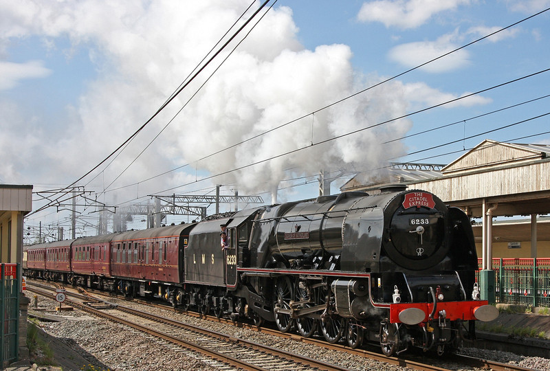 With steam to spare, 6233 (in post-war LMS black) re-starts the 'Citadel Express' from its Carnforth water stop and  digs in for the northbound assault on the Cumbrian Fells.  8th May 2010.