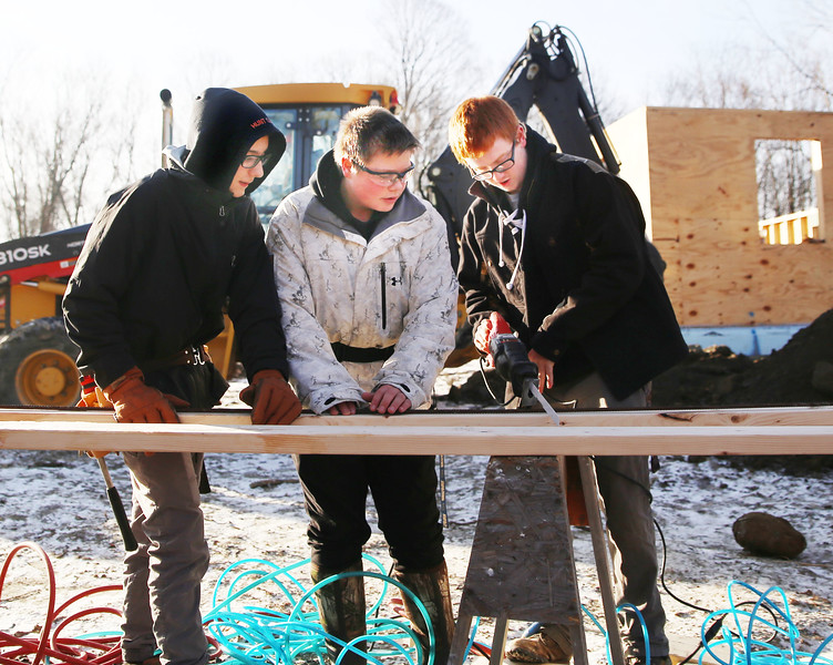 HOLLY PELCZYNSKI - BENNINGTON BANNER CDC Juniors, Evan Harrington, Colby Babson, and Colby Martocchio work together on the habitat for humanity job site on Branch St. in Bennington on Friday morning.