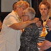 Associate Director Donna Esposito gives new Associate Reasie her medal