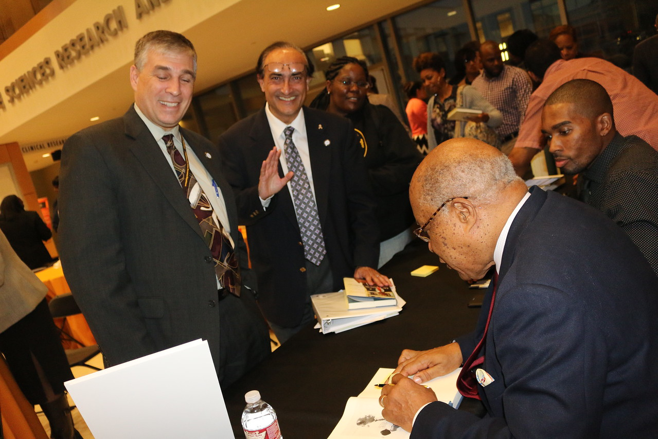 Dr. Vadgama (waving) heads CDU Research about to get his book signed