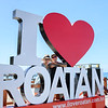 "Happy couple standing behind ""I Love Roatan"" sign, West End Village, Roatan, Honduras"