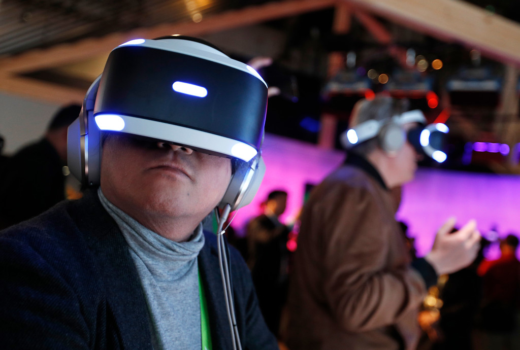 . People look through Sony PlayStation VR headsets after a Sony news conference at CES International, Monday, Jan. 8, 2018, in Las Vegas. (AP Photo/John Locher)