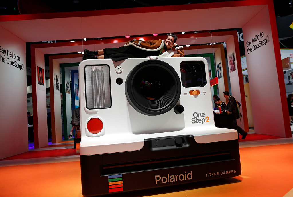 . Loretta Wang waits to have her picture taken at the Polaroid booth during CES International, Tuesday, Jan. 9, 2018, in Las Vegas. (AP Photo/John Locher)