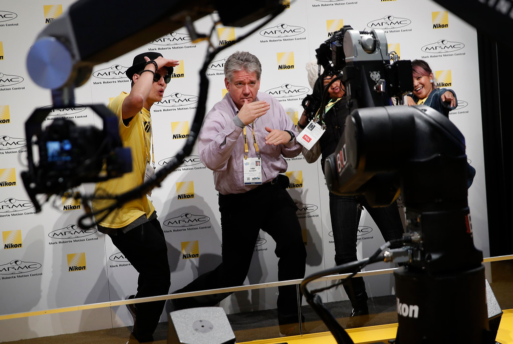 . Kirk Clyatt, center, dances for remote cameras at the Nikon booth during CES International, Tuesday, Jan. 9, 2018, in Las Vegas. (AP Photo/John Locher)