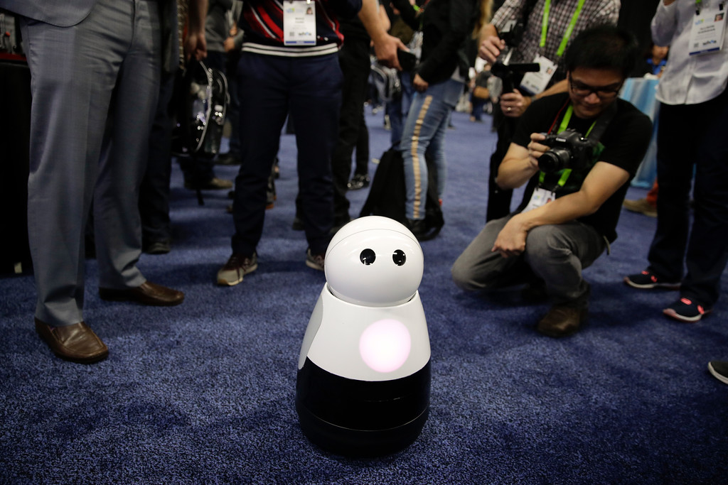 . Mayfield Robotics\' Kuri home robot is surrounded by attendees during CES Unveiled at CES International Sunday, Jan. 7, 2018, in Las Vegas. (AP Photo/Jae C. Hong)