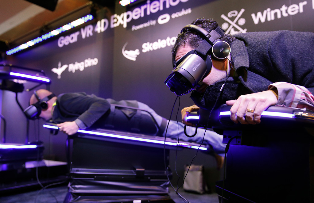 . People experience a skeleton ride with the Samsung Gear VR virtual reality goggles at the Samsung booth during CES International, Tuesday, Jan. 9, 2018, in Las Vegas. (AP Photo/John Locher)