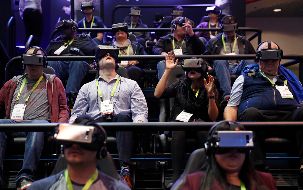 . People look through Samsung Gear VR virtual reality goggles at the Samsung booth during CES International, Tuesday, Jan. 9, 2018, in Las Vegas. (AP Photo/John Locher)