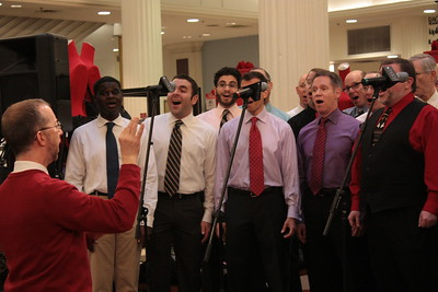 """Chicago Gay Men's Chorus at Macy's """"Believe Day"""" on Friday, December 10, 2010.    Caption:  Patrick Sinozich, Artistic Director of Chicago Gay Men's Chorus, conducts members of the chorus at Macy's Believe Day on December 10, 2010.    Photo Credit: Rick Aiello/Steven Sisk"""