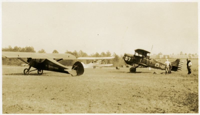 "1.  The airplane on the left has ""Monocoupe"" on its side.  According to Wikipedia, the Monocoupe Corporation was founded in July 1934.  The airplane on the right is labeled U.S. ARMY / CURTISS 0 1B / A.C 27-273.  This is a variety of the Curtiss Falcon, ""a family of military biplane aircraft built by the Curtiss Aeroplane and Motor Company during the 1920s. Most saw service as part of the United States Army Air Corps as observation aircraft ... or as the attack aircraft designated the A-3 Falcon."" (Wikipedia)."