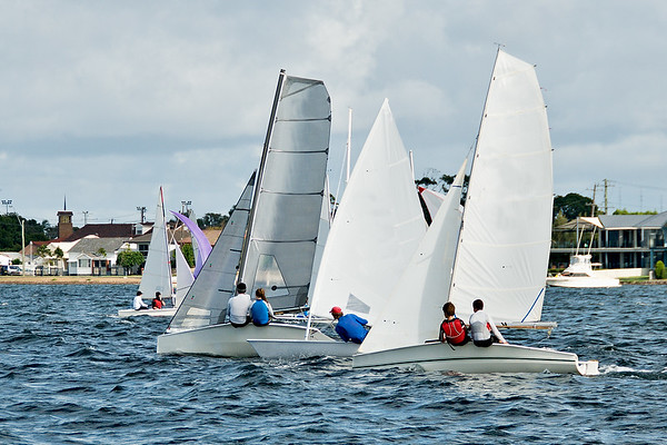 Children Sailing small sailboat in close compettion on an inland