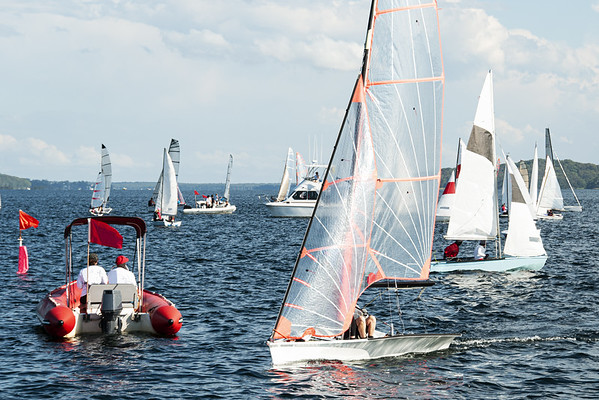 Childrens yacht race starting boat mingling with competing saleb