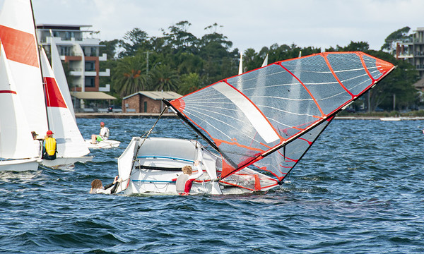Children climbing back into a capsized sailboat with on an inlan
