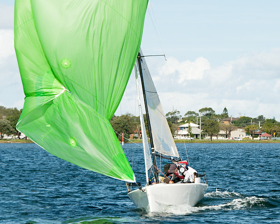 Kids sailing small sailboat head-on closeup with a fouled green spinnaker.