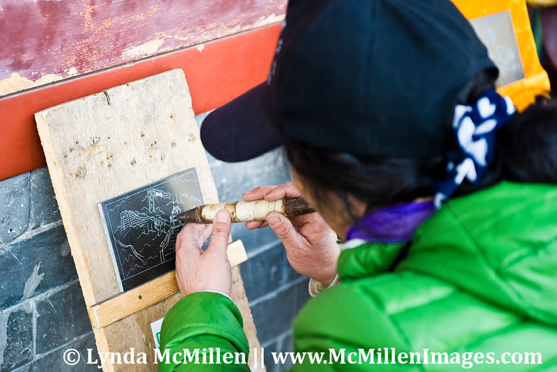 """An artist """"carving"""" Great Wall images in slate."""