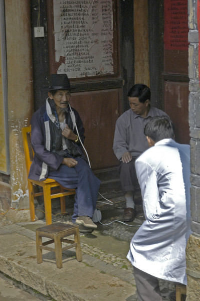 Receiving medical care on the edge of the marketplace in Lijiang.