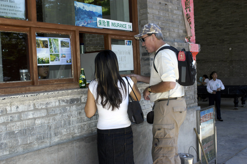 The tour guide assists Dan Simon in purchasing tickets for the gondola ride to the top of the Great Wall.  Insurance is offered for one yuan.