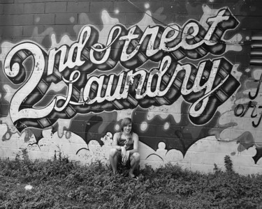 CHRIS CLARK SITTING IN FRONT OF 2ND STREET LAUNDRY B&W