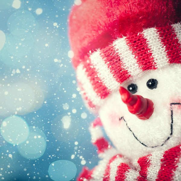 Funny snowman portrait against snowfall, abstract christmas backgrounds