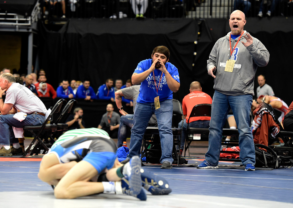 . Broomfield High School coaches Pat DeCamillas, right, and Brandon Madril yell to Presley Madril as he wrestles Grant Bradley, of Overland High School, during a class 5A 106-pound wrestling match during the first day of the CHSAA State Wrestling Championships on Thursday at the Pepsi Center in Denver. More photos: www.BoCoPreps.com Jeremy Papasso/ Staff Photographer/ Feb. 16, 2017