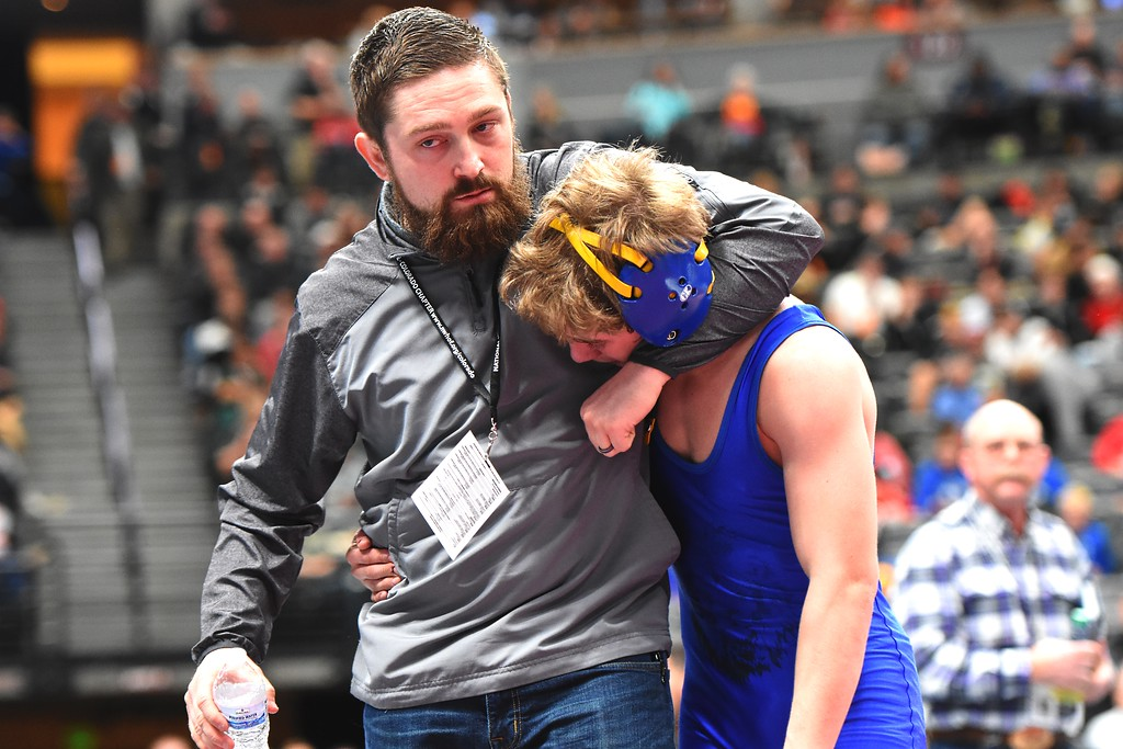. Lyons High School\'s Oran Huff is consoled by Head Coach Head Coach Brandon Lohr after losing to Junior Arambula, of Wray, during a 2A 126-pound match during day 2 of the CHSAA State Wrestling Tournament  on Friday at the Pepsi Center in Denver. More photos: BoCoPreps.com Brad Cochi 02/16/2018