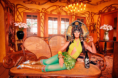 Christina Aguilera, dressed in an outfit reminiscent of Cher, relaxes with a glass of champagne. ca. 2003