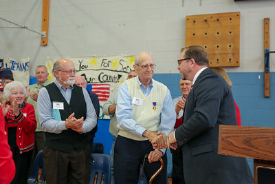 CIS principal Kevin Hanlon shakes the hand or WWII Purple heart winner Clifton Caldon.  Photo by John Fitts