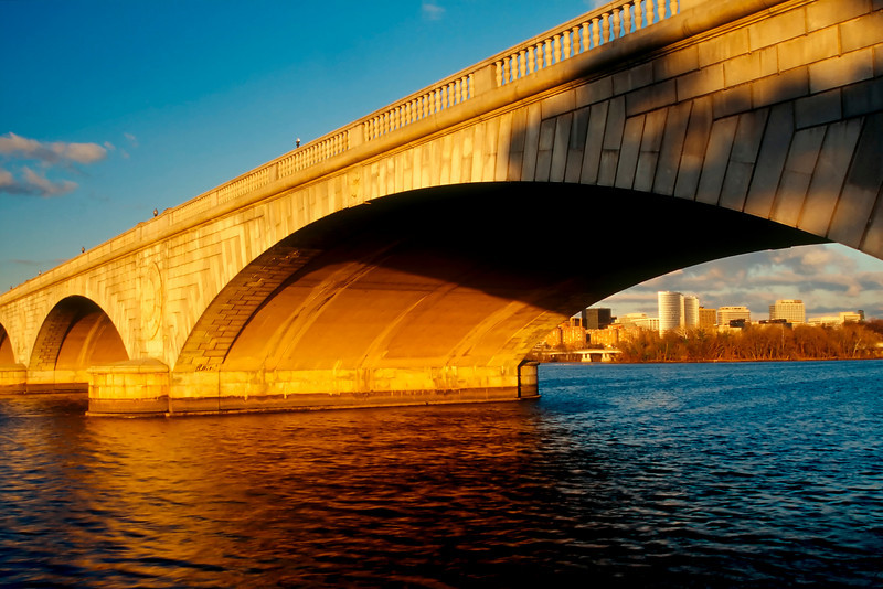 THE ARLINGTON MEMORIAL BRIDGE COLORED BY THE MORNING LIGHT, WITH ROSSLYN VA IN THE BACK GROUND.