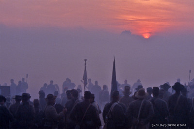 The sun rises; the battlefield is hidden by morning mist and black smoke.