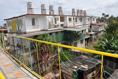 "Patio view of José Fuster's self-tiled home in Jaiminita, Cuba, showing the neighbor's home which says, ""Viva Cuba,"" (Cuba Lives) above."