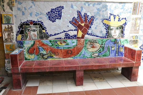 Bench seating area in the outdoor garden of Cuban artist, José Fuster's self designed tiled house in Jaiminita, Cuba.