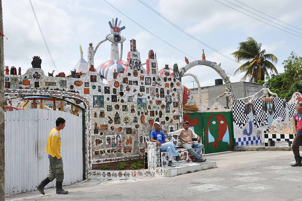 Tile workers sit at the entrance to José Fuster's self-designed tile house in Jaiminita, Cuba.