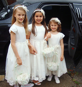 Flower girls prepare to go to the wedding ceremony in front of the limosine.