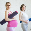 Group of pregnant fitness women holding sport mats