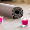 Folded brown yoga, pilates mat on the floor with lighted rose candles around. Close up