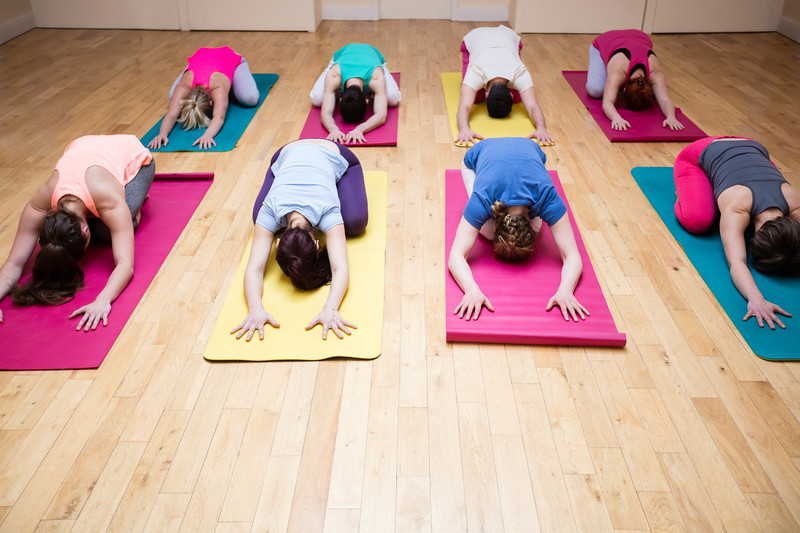 Group of people performing childs pose yoga exercise