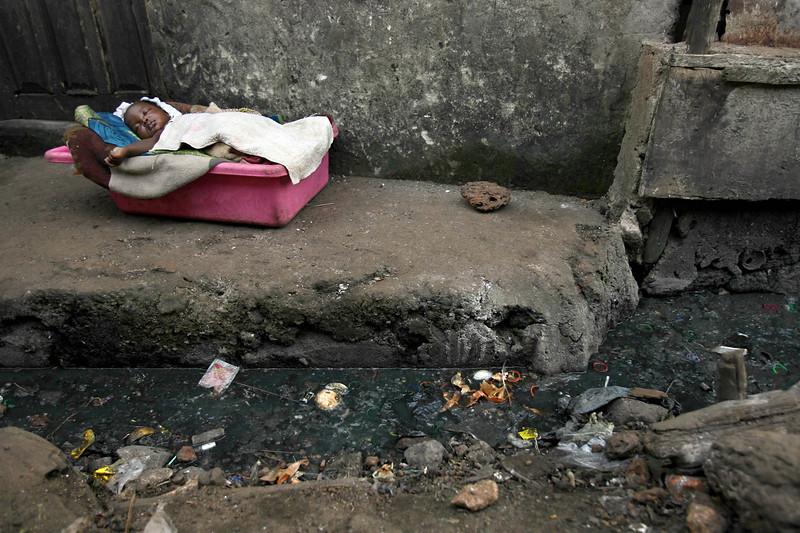 Zainab Kamara, 2 months, sleep by a  sewage filled gutter in Susan's Bay slum in Freetown, Sierra Leone, November 11, 2008.