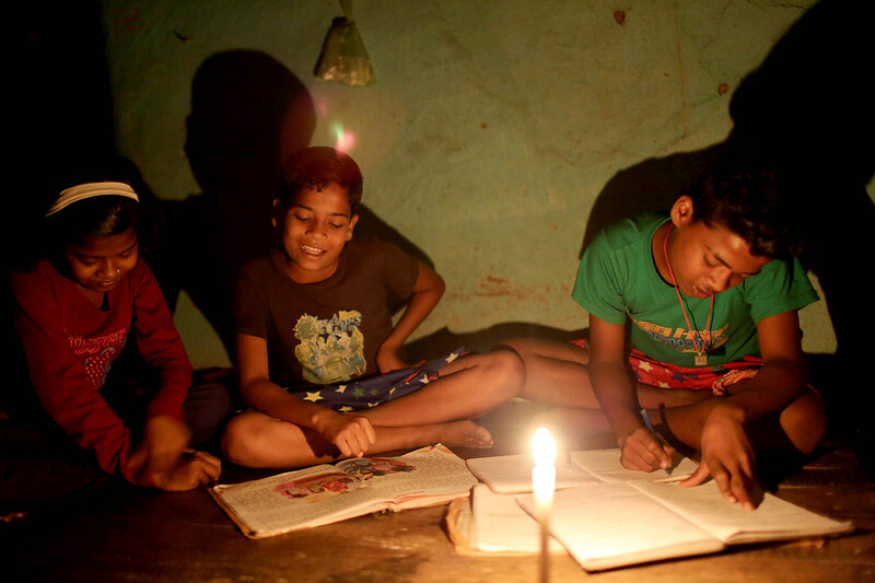 Siblings Antra Kumari, 10, left, Om Kumar, 9, and Karan Kumar, 13, study in their home in the village of Kalimela in Jharkhand state, India, October 28, 2018. Their village lacks electricity.