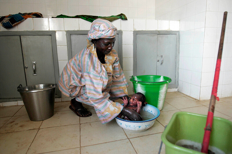 A custodian washes a baby at the Maternity Hospital in Kabala, Sierra Leone, November 24, 2008.